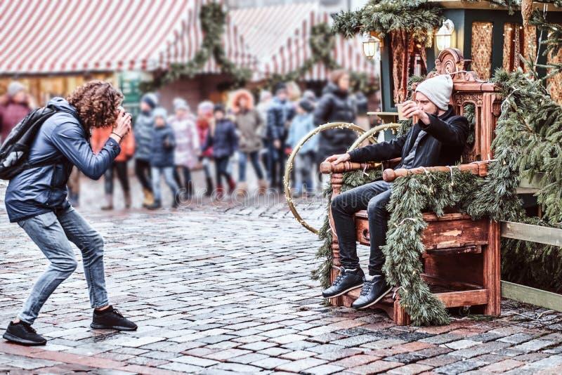Fotograaf in het stadsvierkant die een vriend fotograferen stock fotografie