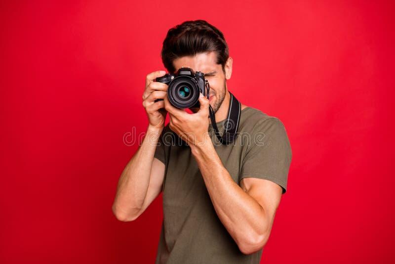 Fotograaf met foto-digicam die foto's maakt draagt een klein grijs T-shirt dat geïsoleerd is op rode achtergrond royalty-vrije stock foto