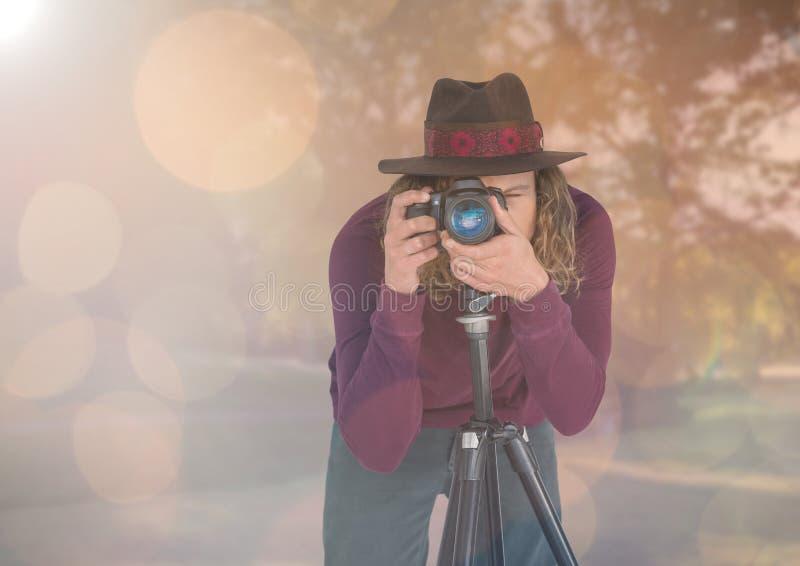 fotograaf met hoed die een foto met driepoot in het park nemen Lichten en gloed stock fotografie
