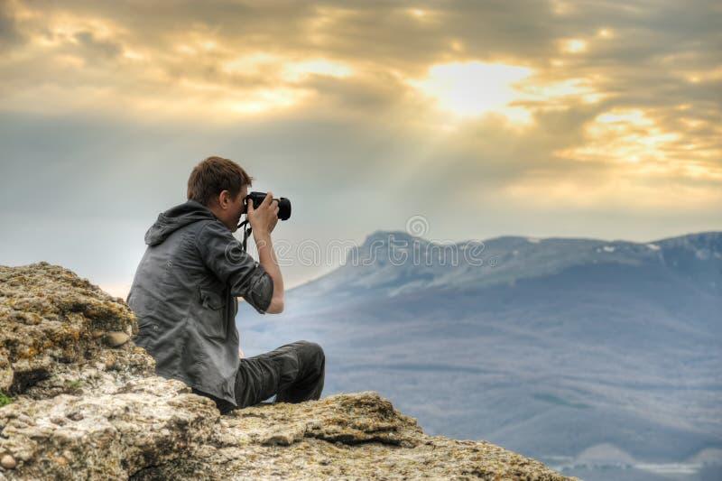 Fotograaf op rots stock afbeeldingen