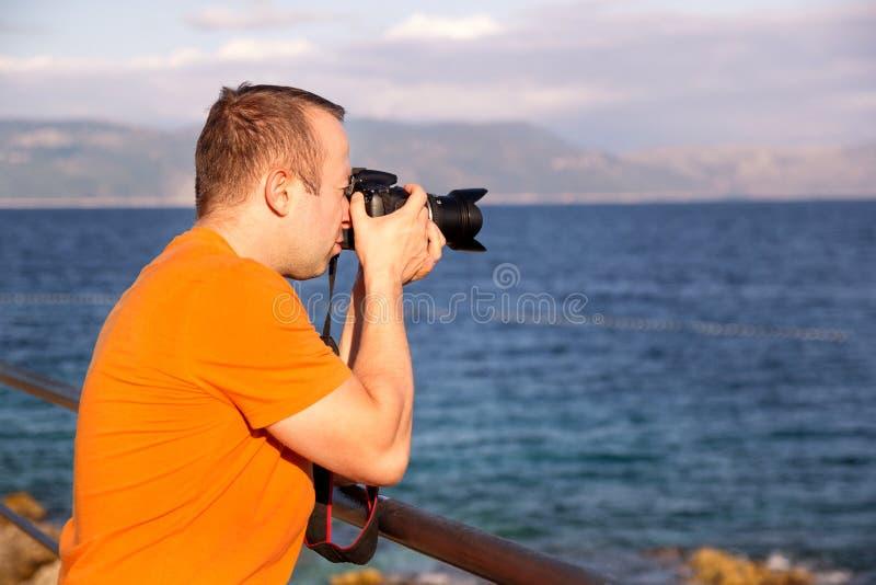 Fotograaf op strand, de zomertijd / Kerelstoerist in aard die Middellandse foto's Adriatische Zee nemen, royalty-vrije stock afbeelding