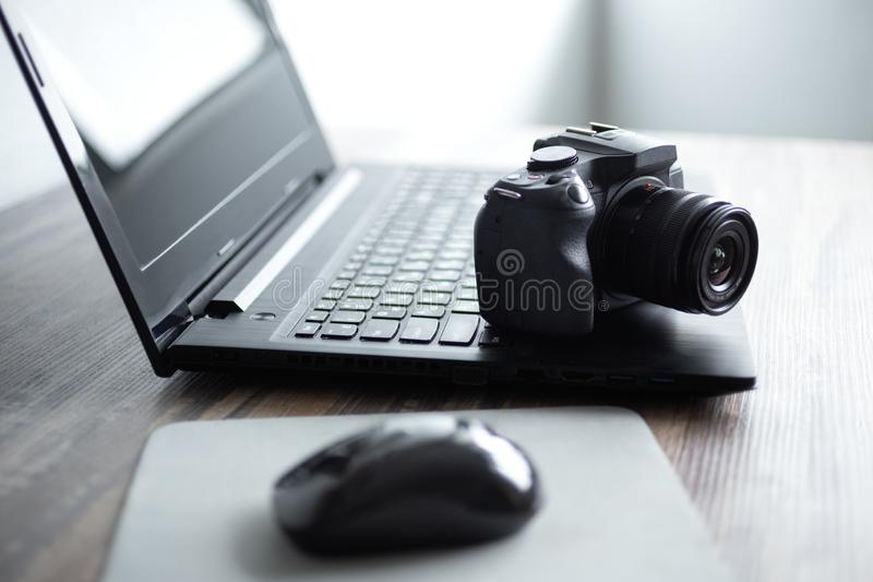 Fotograaf of voorraadfotografieconcept, digitale zwarte camera dichtbij laptop op bureauwerkstation stock foto