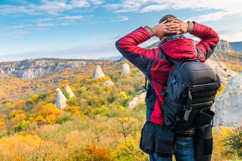 Fotograafreiziger met een rugzak die mooie bergen in de herfst bewonderen stock afbeelding