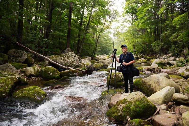 Fotograafreiziger op een bergrivier stock afbeeldingen