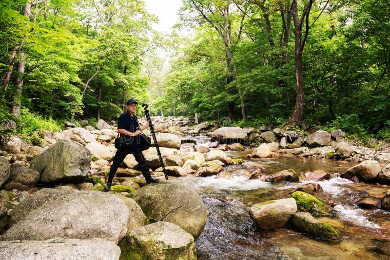 Fotograafreiziger op een bergrivier stock foto's
