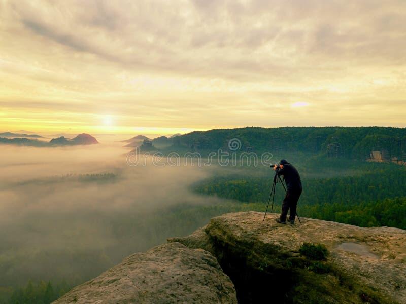 Fotograafsilhouet boven een wolkenoverzees, nevelige bergen royalty-vrije stock afbeelding