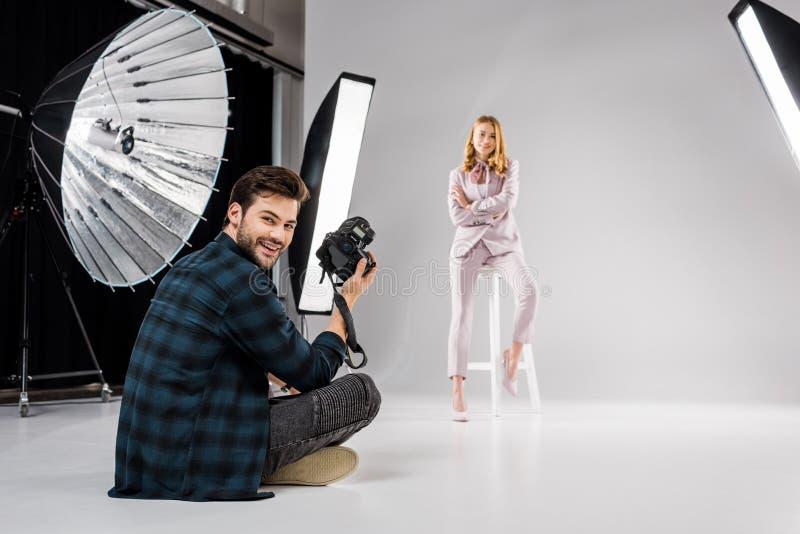 fotograafzitting en het glimlachen bij camera terwijl het mooie vrouwelijke model stellen stock afbeelding