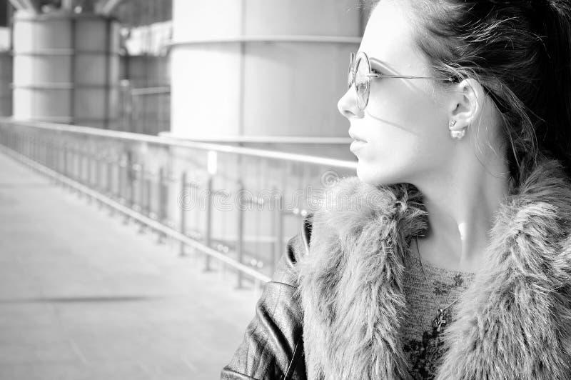 Fotografía blanca negra de la señora joven hermosa en el fondo de cristal del edificio de la ciudad fotos de archivo