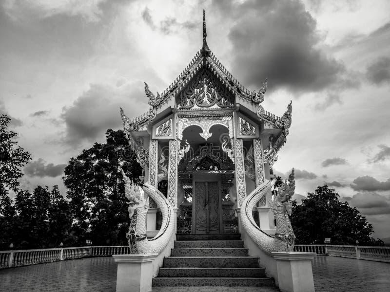 Fotografía blanco y negro con poco templo blanco budista con nadie y el cielo nublado dramático en atmósfera oscura fotografía de archivo libre de regalías