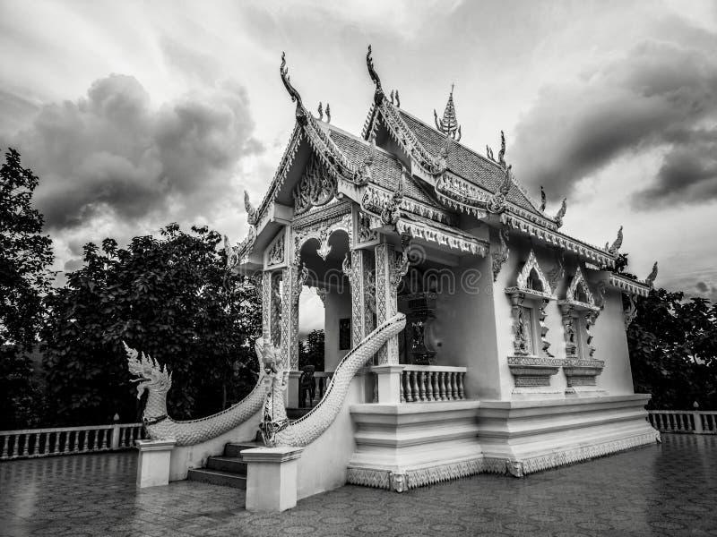 Fotografía blanco y negro con poco templo blanco budista con nadie y el cielo nublado dramático en atmósfera oscura imágenes de archivo libres de regalías