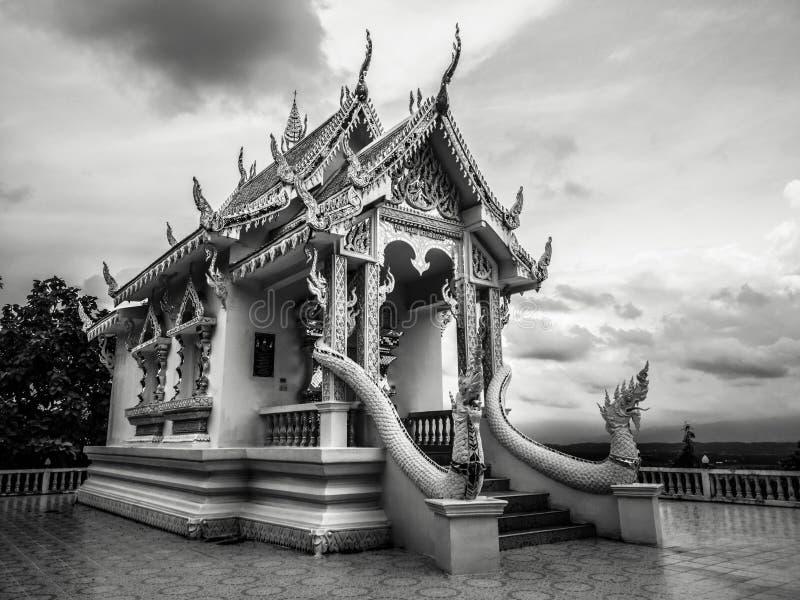 Fotografía blanco y negro con poco templo blanco budista con nadie y el cielo nublado dramático en atmósfera oscura imagen de archivo