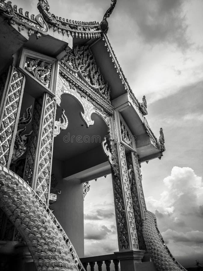 Fotografía blanco y negro con poco templo blanco budista con nadie y el cielo nublado dramático en atmósfera oscura fotografía de archivo