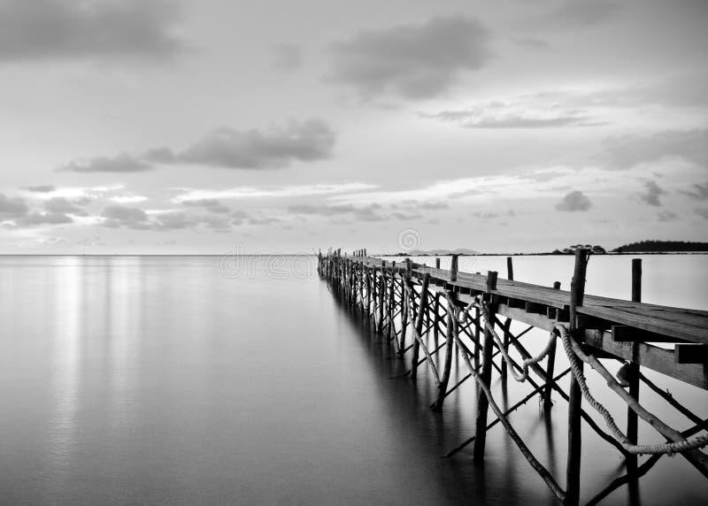 Fotografía blanco y negro de un embarcadero de madera de la playa