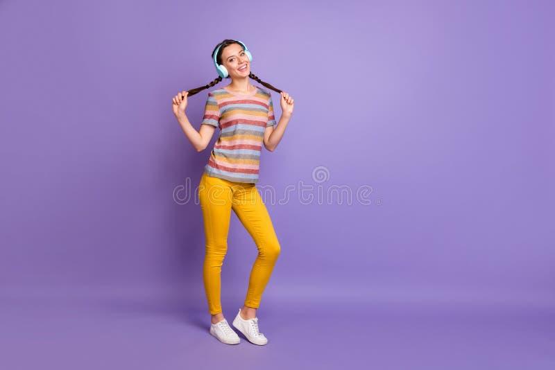 Fotografía completa de una chica positiva alegre relajarse escuchar música rítmica melodía de los auriculares inalámbricos azul d imagenes de archivo