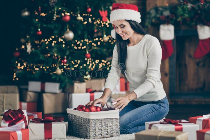 Fotografía completa de una chica positiva en santa claus que se sienta alfombra ordenar Navidad y bolas de árbol prepararse para fotos de archivo
