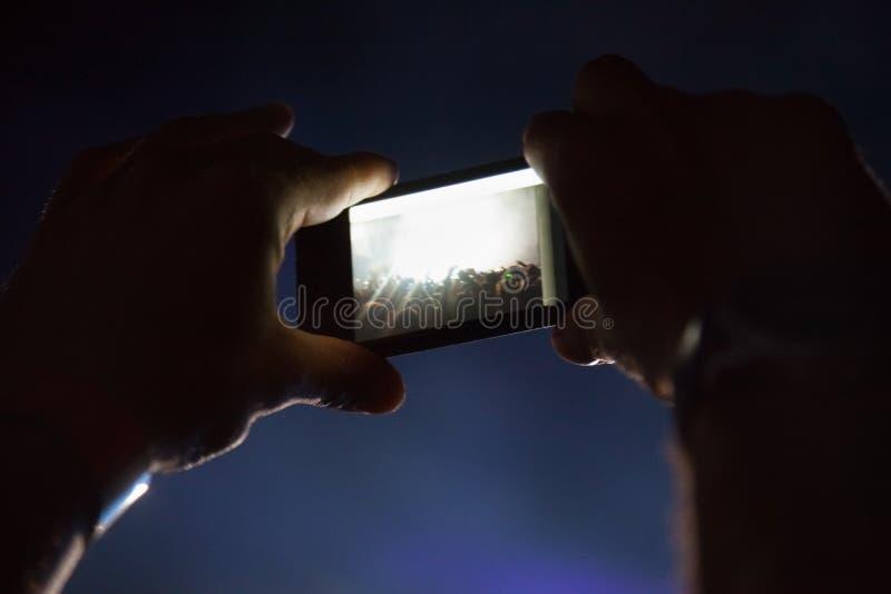 Fotografía con el teléfono celular en el concierto fotos de archivo libres de regalías