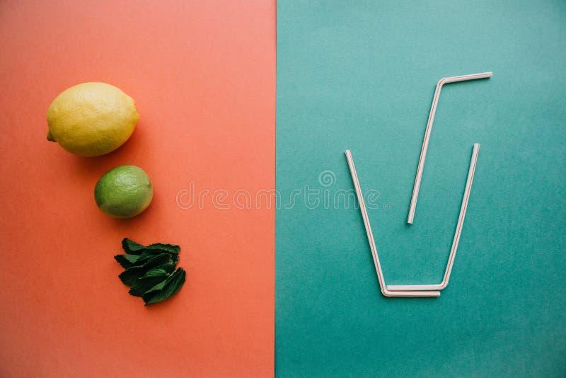 Fotografía conceptual Limonada o jugo de la fruta cítrica En un lado al vidrio de tubos En el otro lado es el limón fresco, cal imagen de archivo