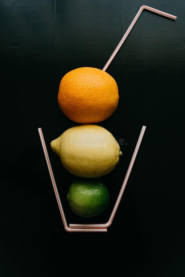 Fotografía conceptual Limonada o jugo de la fruta cítrica de las frutas frescas en un vidrio de tubos fotografía de archivo libre de regalías