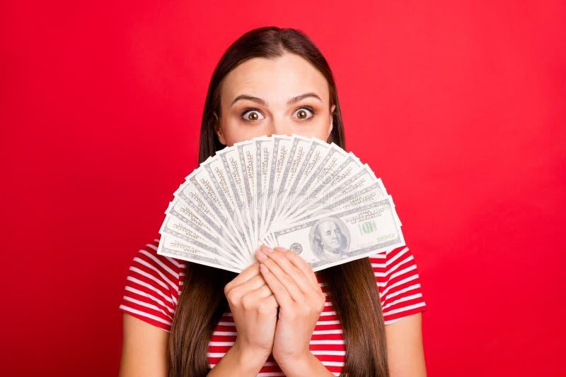 Fotografía de cerca de una linda chica linda con una camiseta a rayas sosteniendo dinero con sus manos escondiéndose detrás de  imagen de archivo