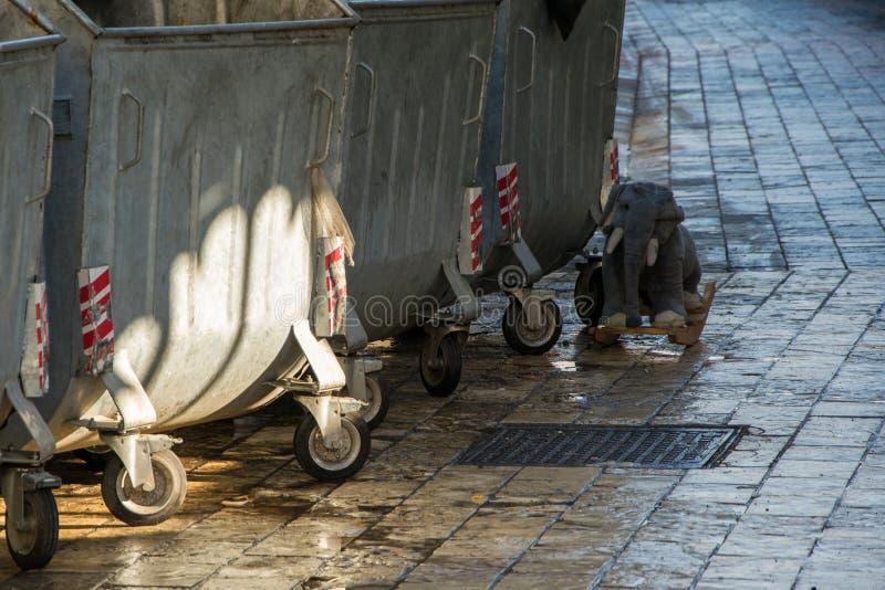 Fotografía de la calle - juguete oscilante viejo para los niños lanzados cerca de los compartimientos de los desperdicios fotografía de archivo libre de regalías