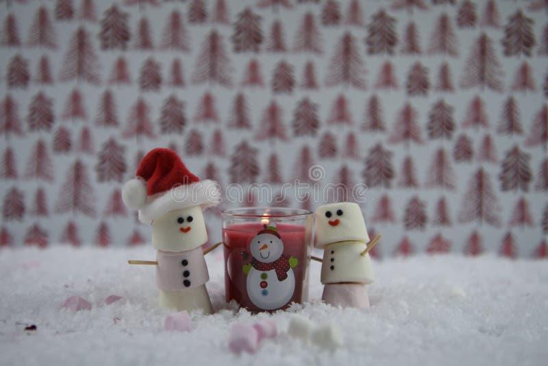 Fotografía de la comida de la Navidad usando las melcochas formadas como muñeco de nieve con helado en sonrisa y vela encendida r imágenes de archivo libres de regalías