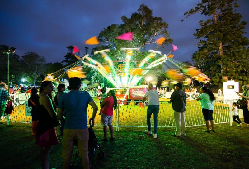 Fotografía de la noche del paseo del oscilación en el movimiento de la velocidad en la feria de diversión de la comunidad, parque imagen de archivo libre de regalías