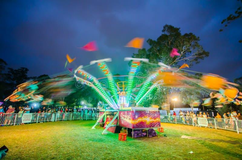 Fotografía de la noche del paseo del oscilación en el movimiento de la velocidad en la feria de diversión de la comunidad, parque foto de archivo