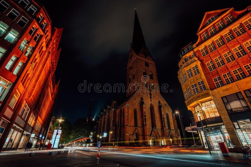Fotografía de la noche de Hamburgo en el cruce Vista de la iglesia del St Petri y de los edificios de ladrillo rojo tradicionales imagen de archivo