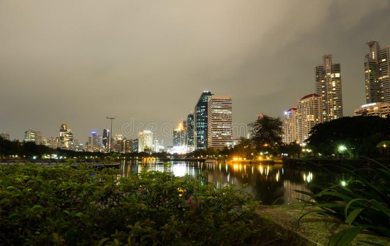Fotografía de la noche de la opinión del rascacielos del centro de Bangkok con su reflexión en el lago del agua en el parque de B imagenes de archivo
