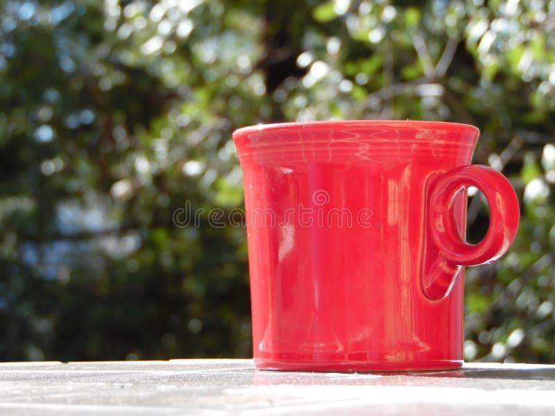 Fotografía de la taza de café roja afuera foto de archivo