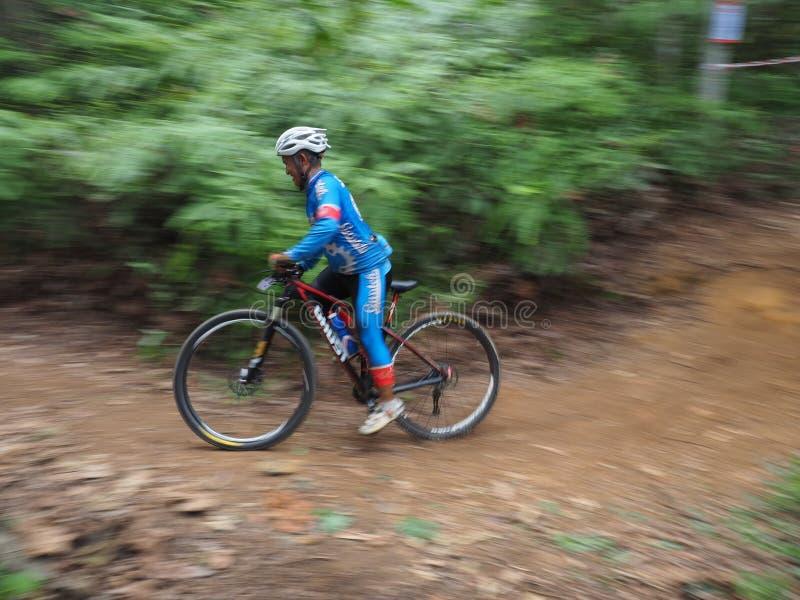 Fotografía de la toma panorámica del cyclin del hombre durante una raza de la bici de montaña foto de archivo libre de regalías