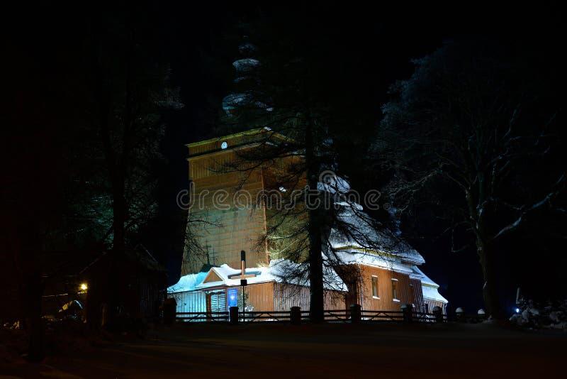 Fotografía de madera iluminada hermosa de la iglesia en el invierno de la noche por completo de la nieve Tylicz Polonia imágenes de archivo libres de regalías