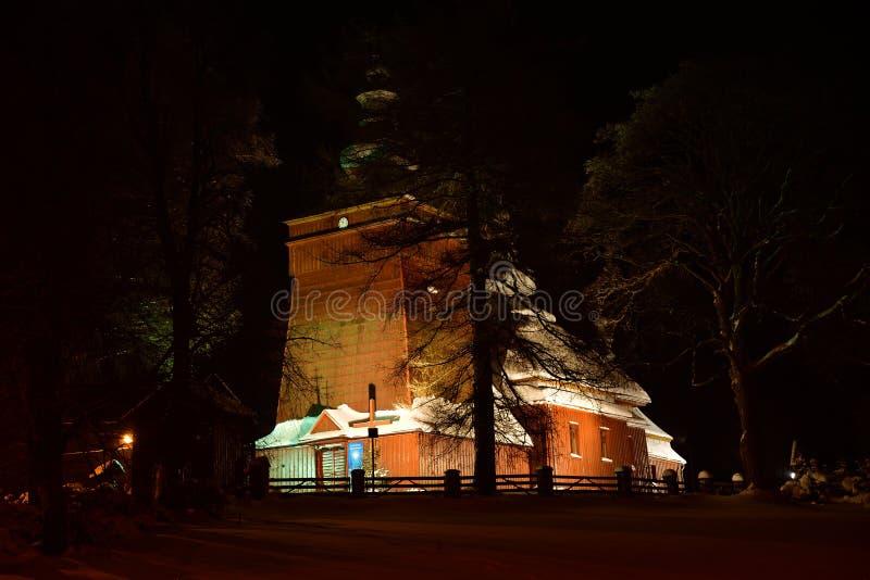 Fotografía de madera iluminada hermosa de la iglesia en el invierno de la noche por completo de la nieve Tylicz Polonia foto de archivo