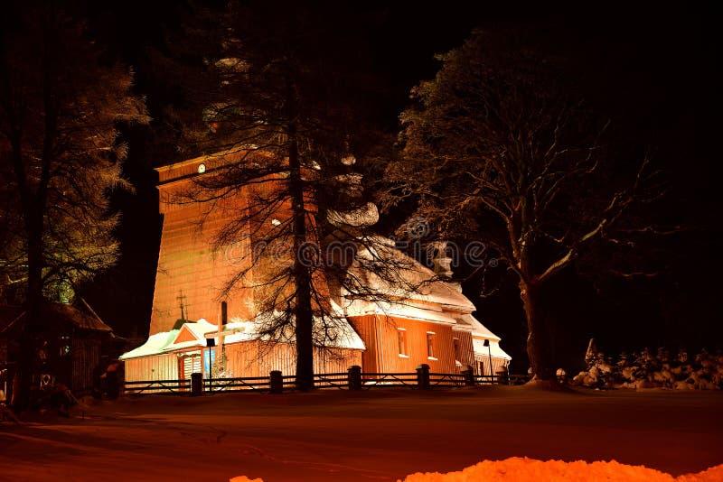 Fotografía de madera iluminada hermosa de la iglesia en el invierno de la noche por completo de la nieve Tylicz Polonia fotografía de archivo libre de regalías