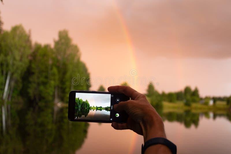 Fotografía de un paisaje en un smartphone Arco iris y puesta del sol rojo-amarilla con la reflexión en una charca del bosque imagenes de archivo