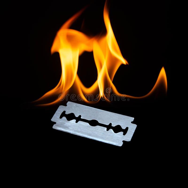 Fotografía de una hoja de afeitar aguda brillante con las llamas imagen de archivo libre de regalías