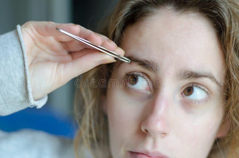 Fotografía de una muchacha que despluma sus cejas con las pinzas fotos de archivo libres de regalías