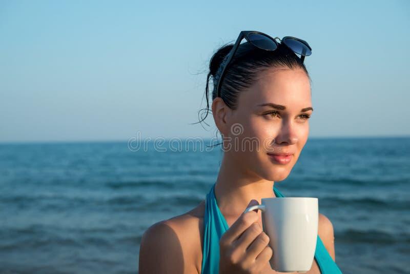 Fotografía de una mujer morena hermosa con la taza blanca con té fotos de archivo libres de regalías