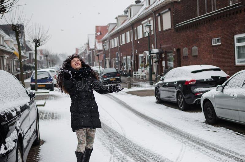 Fotografía de una mujer que juega con nieve en una calle en Holanda fotografía de archivo