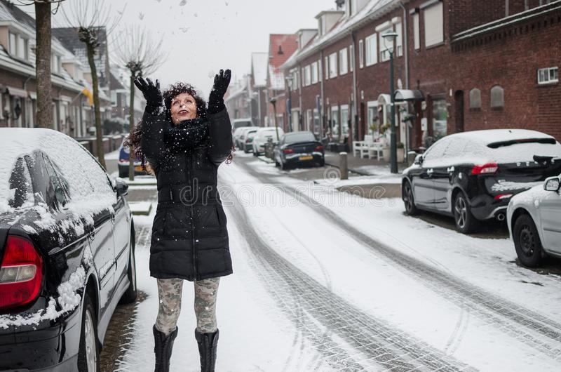 Fotografía de una mujer que juega con nieve en una calle en Holanda fotografía de archivo libre de regalías