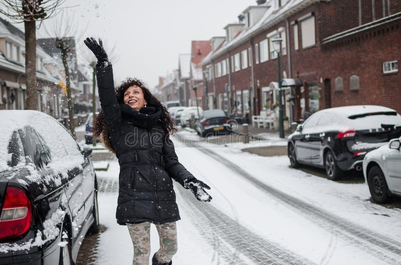 Fotografía de una mujer que juega con nieve en una calle en Holanda fotos de archivo libres de regalías