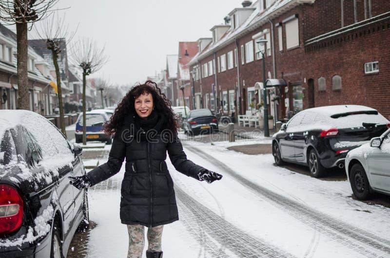 Fotografía de una mujer que juega con nieve en una calle en Holanda imagenes de archivo