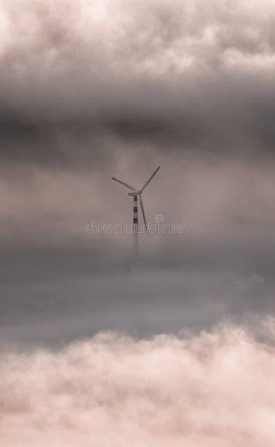 Fotografía del arte: alto de la turbina de viento entre las nubes Imagen romántica de un molino en el cielo Metáfora de la libert imágenes de archivo libres de regalías