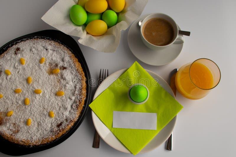 Fotografía del estudio del desayuno o del brunch de Pascua con la torta suiza de Pascua en colores en colores pastel verdes y ama foto de archivo