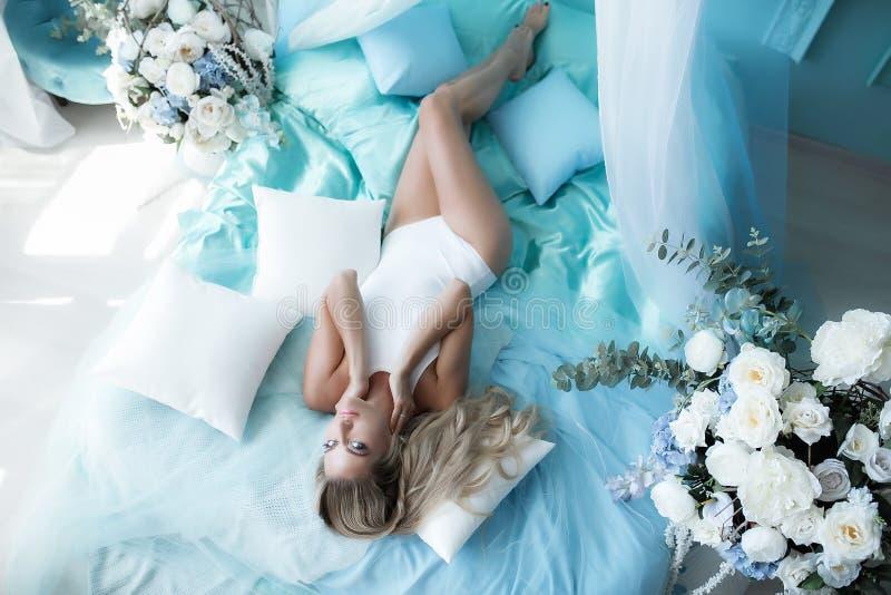 Fotografía del gabinete de señora Mujer rubia con el pelo largo en ropa interior en la cama rodeada por los tulipanes de las flor imagen de archivo