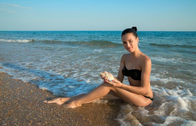 Fotografía del modelo hermoso con la concha marina grande en relaxin de las manos foto de archivo libre de regalías