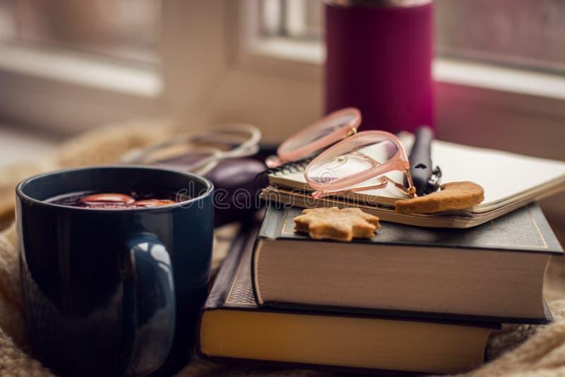 Fotografía del objeto En el libro de la mentira del alféizar, la libreta, la caja de vidrios, las galletas, el termoz y la taza c fotos de archivo