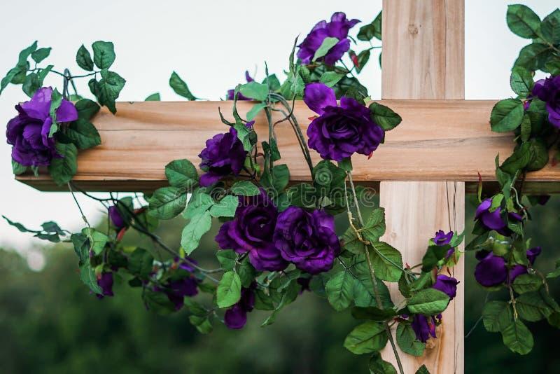 Fotografía del primer de las rosas púrpuras que cuelgan y que envuelven alrededor en una cruz de madera marrón imagen de archivo