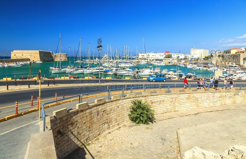Fotografía del viaje: los turistas tragan los barcos de una pesca de la carretera con curvas Puerto de Heraklion, Creta, Grecia fotos de archivo