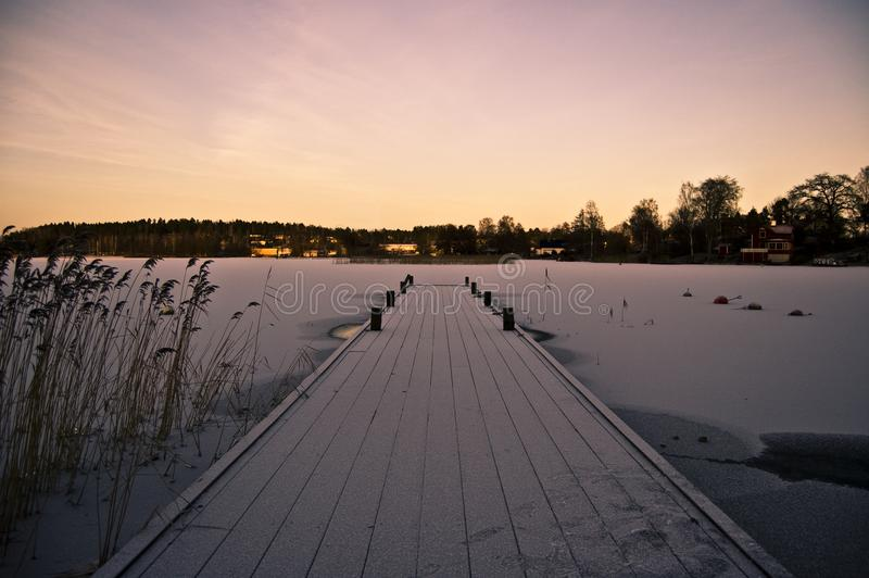 Fotografía estacional del invierno hermoso Embarcadero del barco cubierto en nieve y puesta del sol de la helada grandes/salida d imagen de archivo